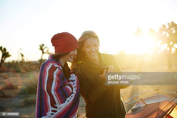 Two young women looking at phone at campsite