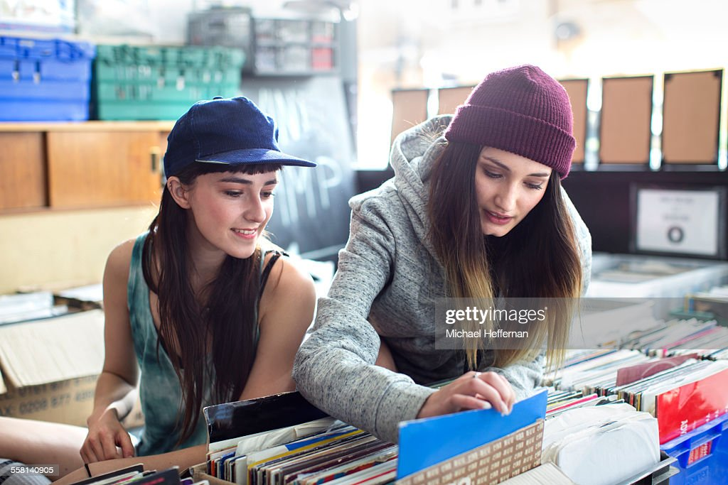 Two young women looking at records in store : Stock Photo
