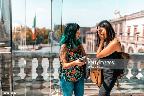 two young women looking at the mobile phone - three quarter length stock pictures, royalty-free photos & images
