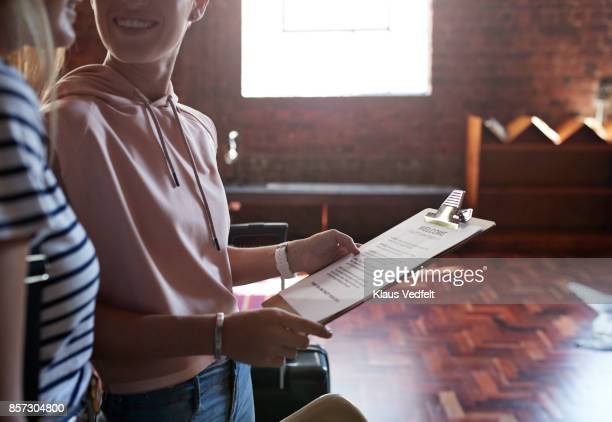 Two young women looking at welcome note, after arriving to rental apartment