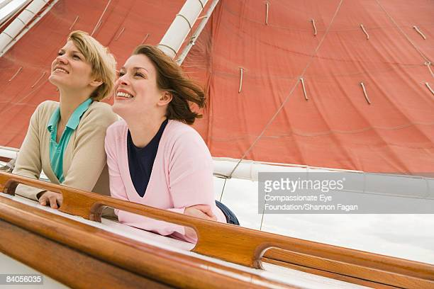 """two young women looking out from sailboat - """"compassionate eye"""" stock pictures, royalty-free photos & images"""