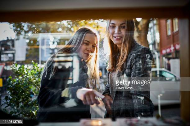 two young women looking through shop window - desire stock pictures, royalty-free photos & images