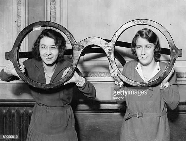 Two young women looking through the world largest eyeglasses exhibit during the large optics exhibition in London Photograph Around 1930 [Zwei junge...