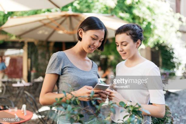 Two young women looking together at smartphone at sidewalk cafe