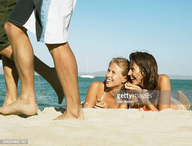 Two young women lying on beach looking at two men passing by, smiling