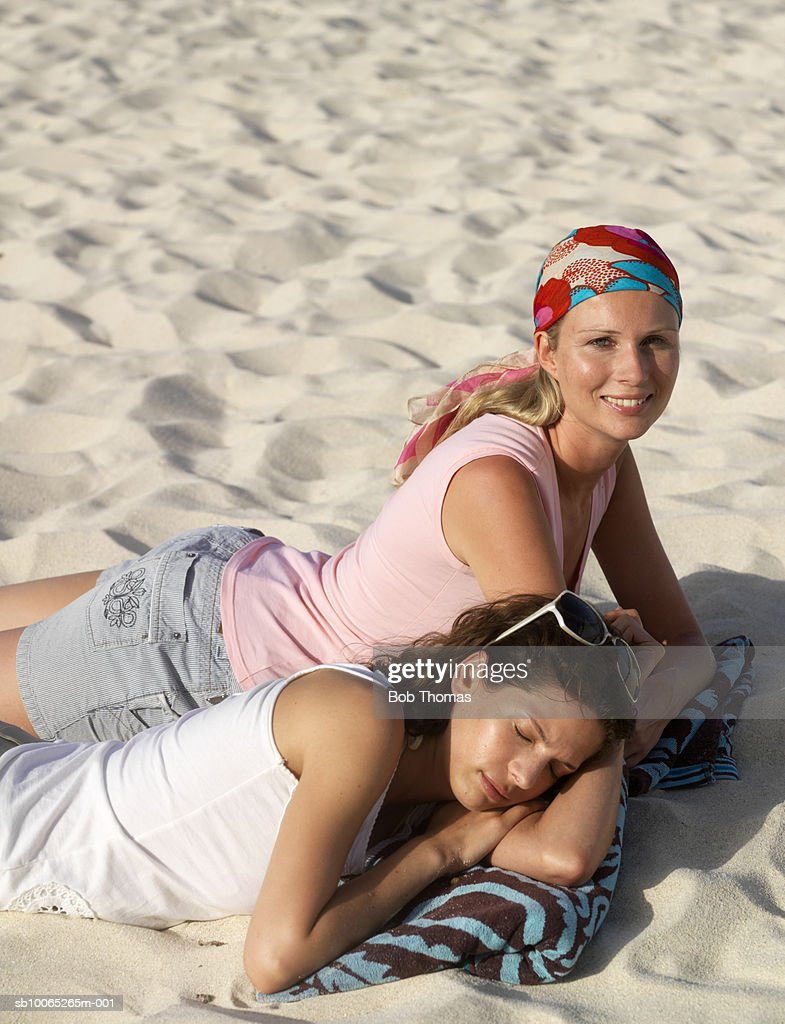 Two young women lying on sand, one sleeping : Foto stock