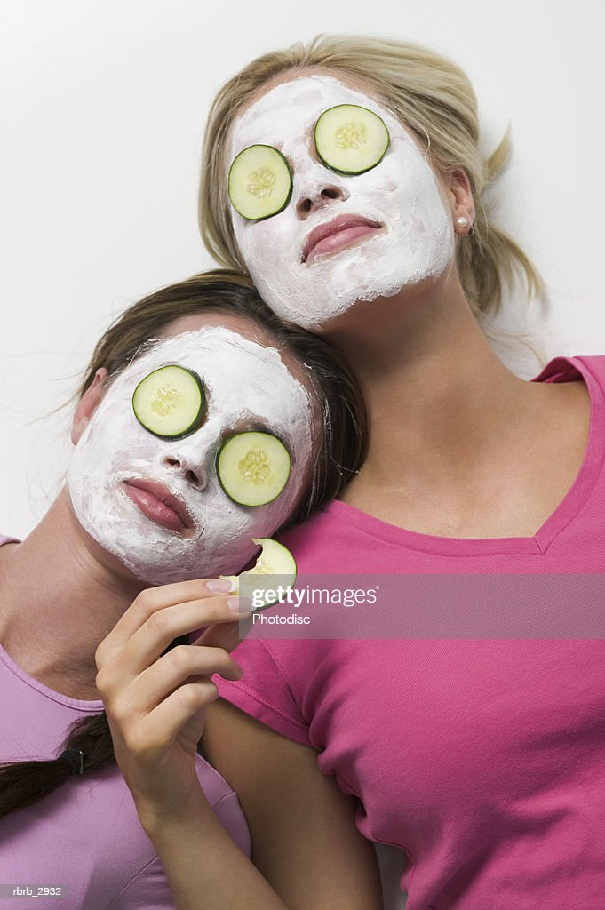 Two young women lying with facial masks and cucumber slices on their eyes : Foto de stock