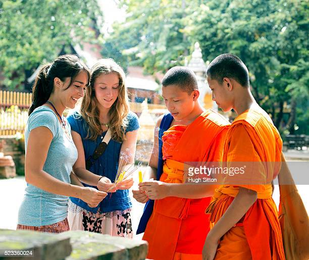 two young women meeting buddhist monks during their travel to asia, chiang mai, thailand - hugh sitton stock pictures, royalty-free photos & images