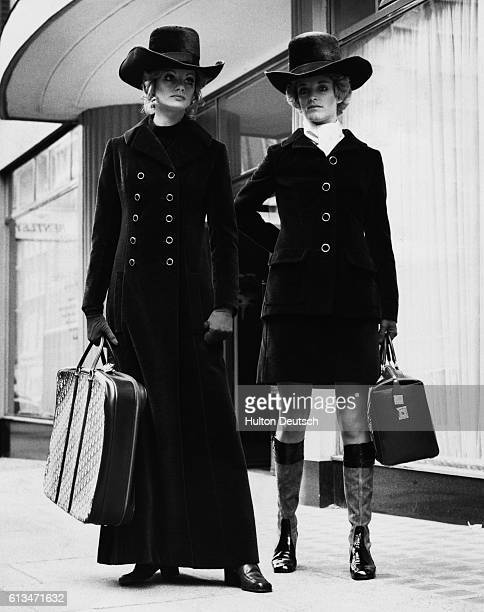 Two young women model outfits designed by Joan Langberg for the Dior London Autumn Collection One wears a long brown velour coat worn over a tunic...