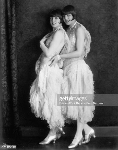 Two young women modelling sleeveless sequinned tops and skirts with ostrich feather trim Hamburg 1924