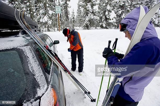 Two young women next to a car with cross country ski's preparing to go Nordic skiing in Bend, Oregon.