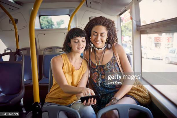 Two young women on a bus listening to music on smart phone