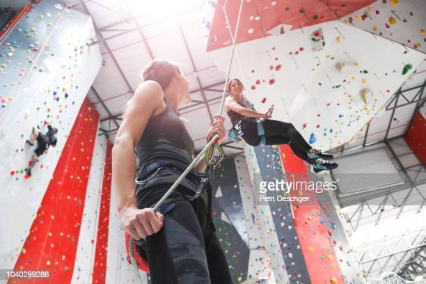 two young women on an indoor climbing wall. - messa in sicurezza foto e immagini stock