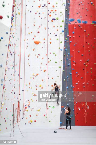 Two young women on an indoor climbing wall.
