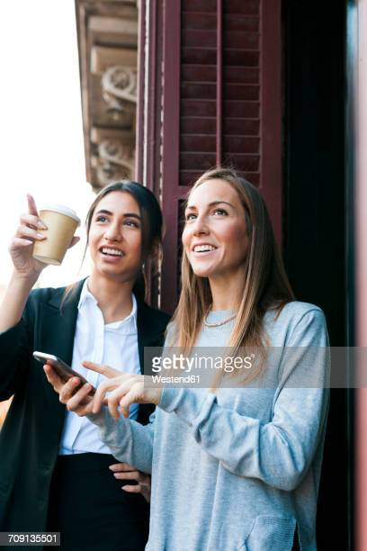 Two young women on balcony with cell phone and takeaway coffee looking up