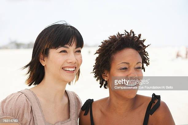 two young women on beach, looking away and smiling, head and shoulders - compassionate eye foundation stock pictures, royalty-free photos & images