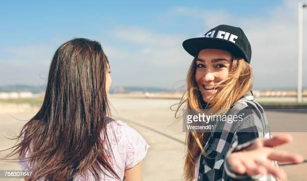 two young women on beach promenade - gesticulando fotografías e imágenes de stock