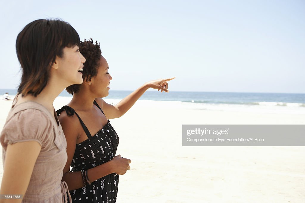 Two young women on beach, smiling, side view, upper half : Foto de stock