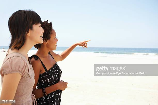 Two young women on beach, smiling, side view, upper half