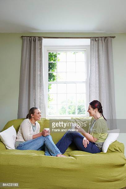 Two young women on couch, with mugs