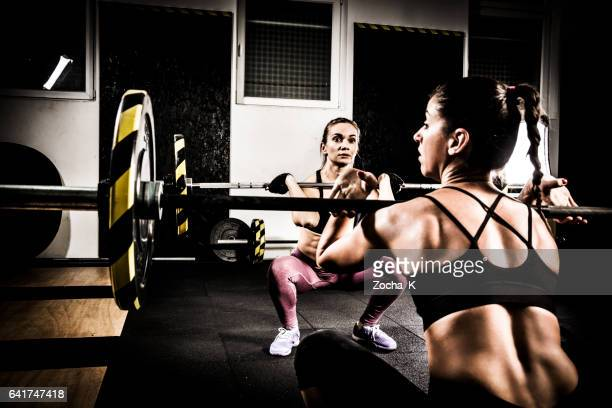 Two young women on cross training lifting weights in gym