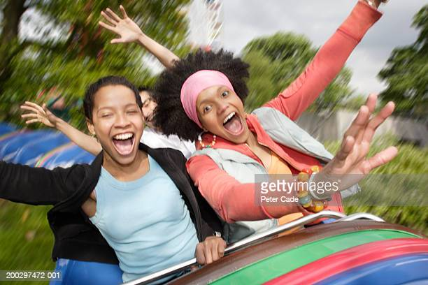Two young women on fairground ride holding arms out, laughing