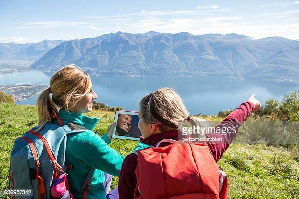 Two young women on mountain top using digital map