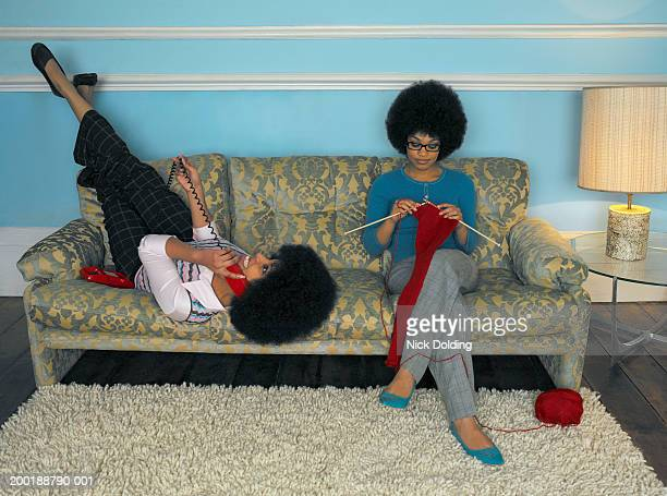 Two young women on sofa, one using telephone, other knitting
