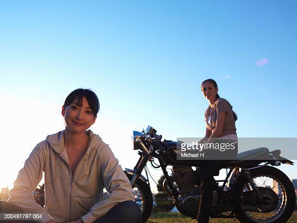 Two young women, one sitting on lawn, one sitting on motorcycle