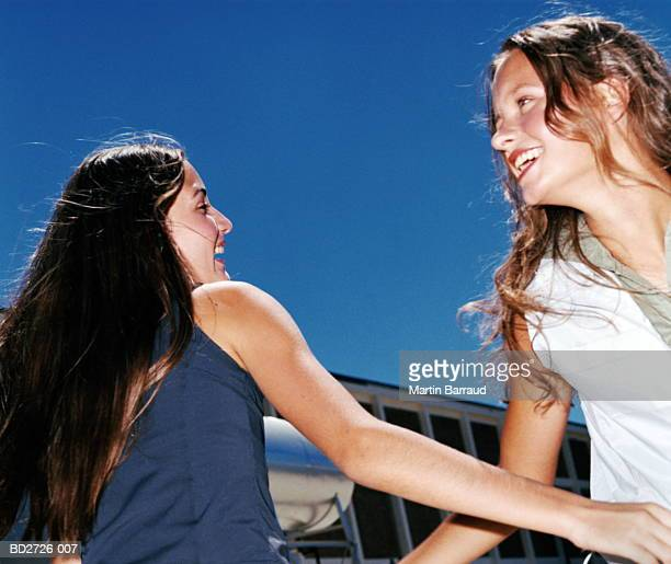 Two young women outdoors, smiling, close-up