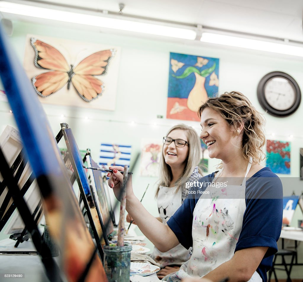 Two young women painting fine art together in a studio : Stock Photo