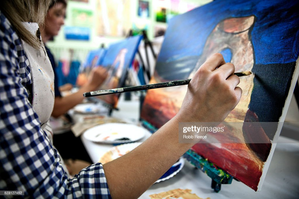Two young women painting on fine art canvas together in a studio : Stock Photo