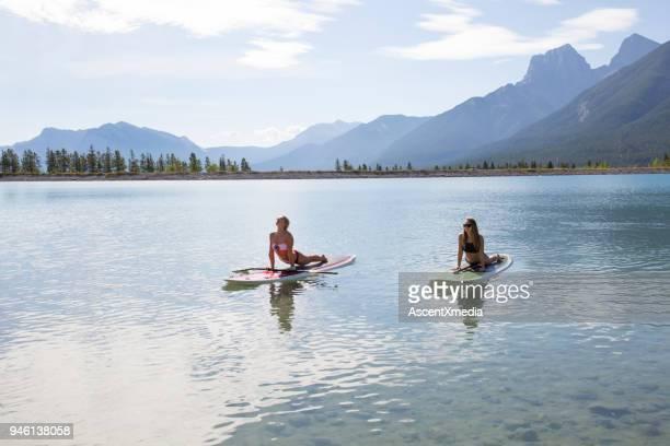 Dos mujeres jóvenes realizan movimientos de yoga en tablas de pádel en el lago de montaña