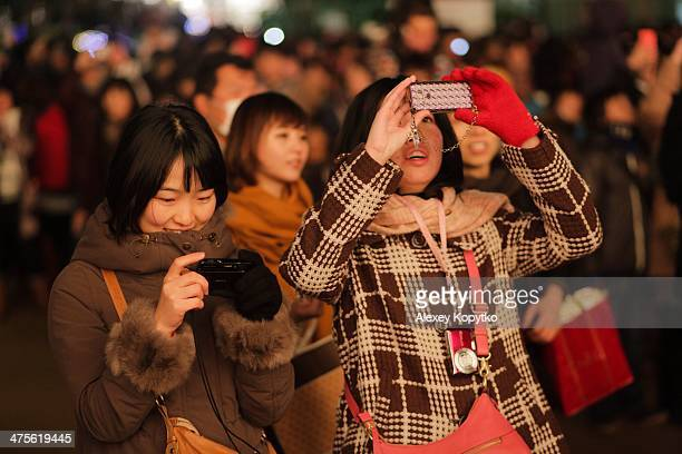 Two young women photograph and check on their smartphone smiling at Kobe Luminarie Japan