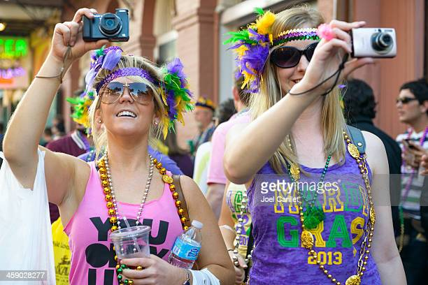 two women photographing mardi gras in new orleans - mardi gras fun in new orleans stock photos and pictures