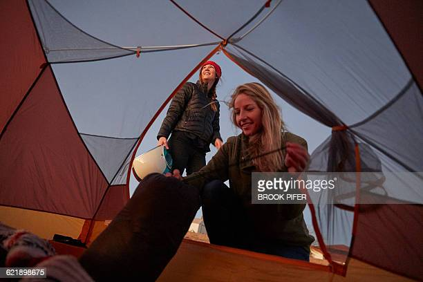 Two young women pitching tent