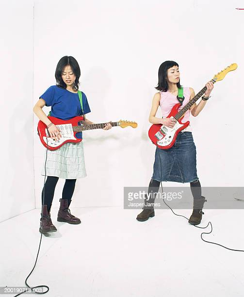 two young women playing electric guitars - girl band stock pictures, royalty-free photos & images