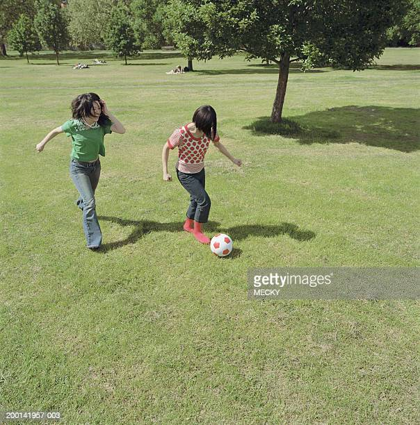 Two young women playing football in park, laughing