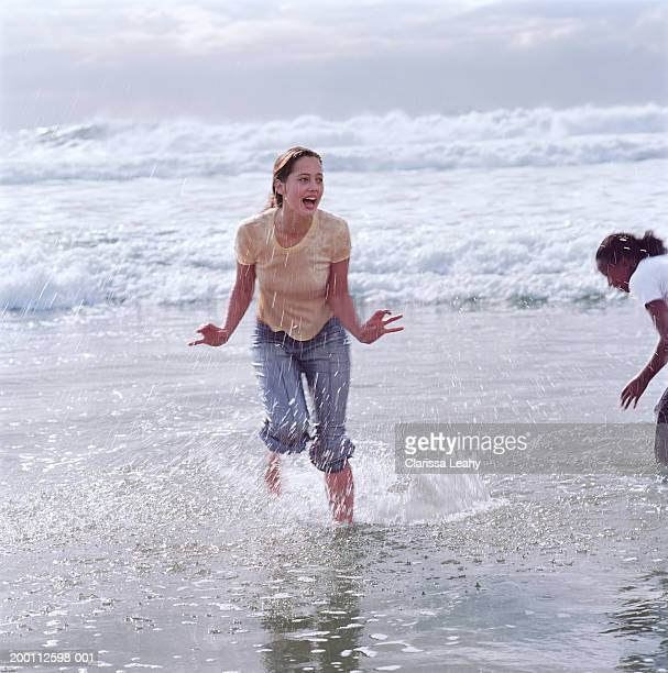 two young women playing in surf - wet t shirts - fotografias e filmes do acervo