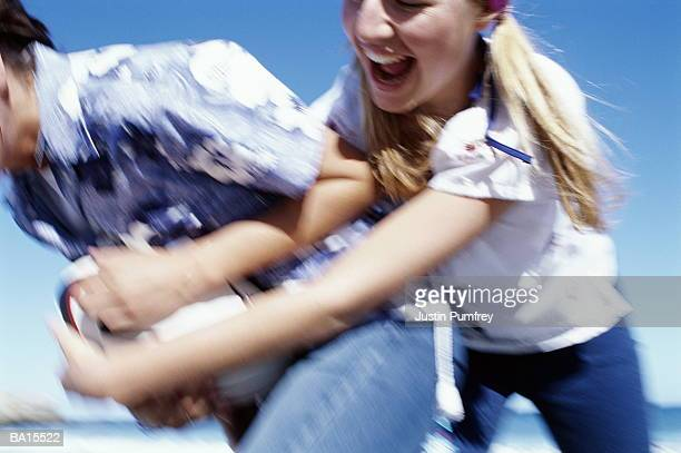 Two young women playing rugby on beach, close-up (defocussed)