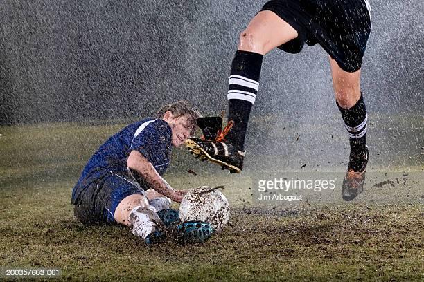 two young women playing soccer in rain - solo adulti foto e immagini stock