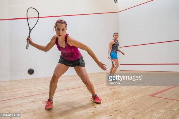two young women playing squash game - squash sport stock pictures, royalty-free photos & images