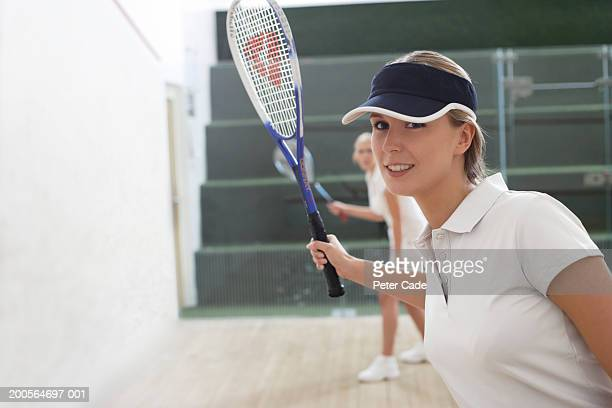 Two young women playing squash, portrait