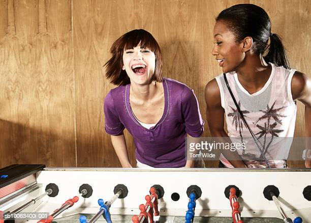 Two young women playing table football, laughing