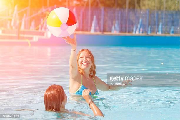 Zwei junge Damen spielen mit ball am Swimmingpool