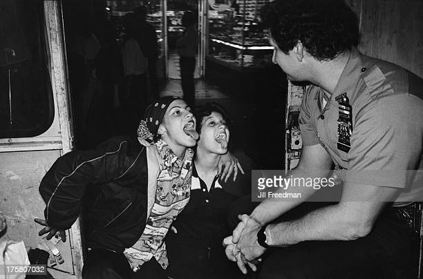 Two young women poke out their tongues at a police officer waiting in a police van on 42nd Street New York City 1979