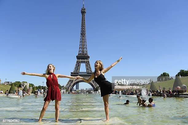 TOPSHOT Two young women pose at the Trocadero fountains in front of the Eiffel tower in Paris as summer temperature raises on July 19 2016 / AFP /...