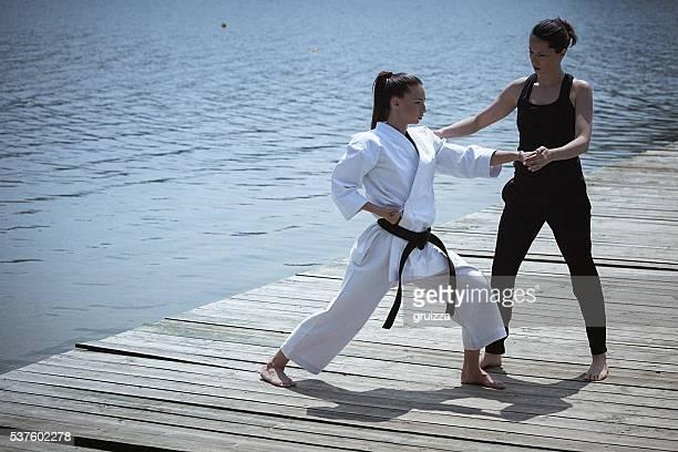 2 つの若い女性 練習 空手屋外