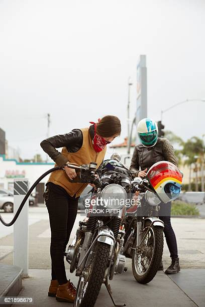 Two young women pumping gas for motorcycle ride