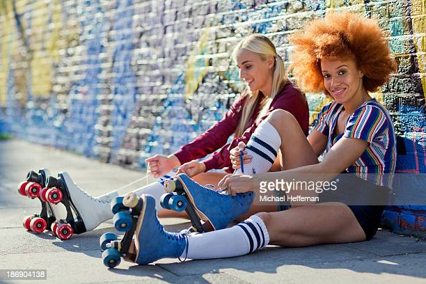 two young women putting on rollerskates